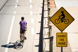 """UW-Madison bicyclist riding on the road in bike lane near a road sign that contains a bicyclist symbol and """"SHARE THE ROAD"""""""
