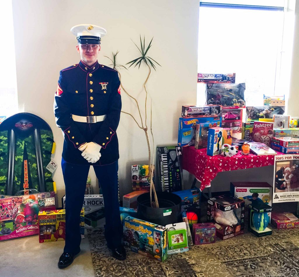Person dressed in military uniform stands with hands clasped looking straight ahead while standing in front of an indoor plant and a large pile of toys
