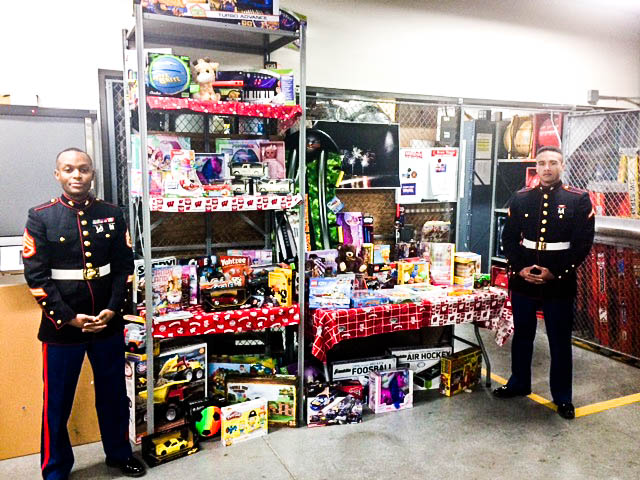 Marines standing near tall shelf stacked with many toys