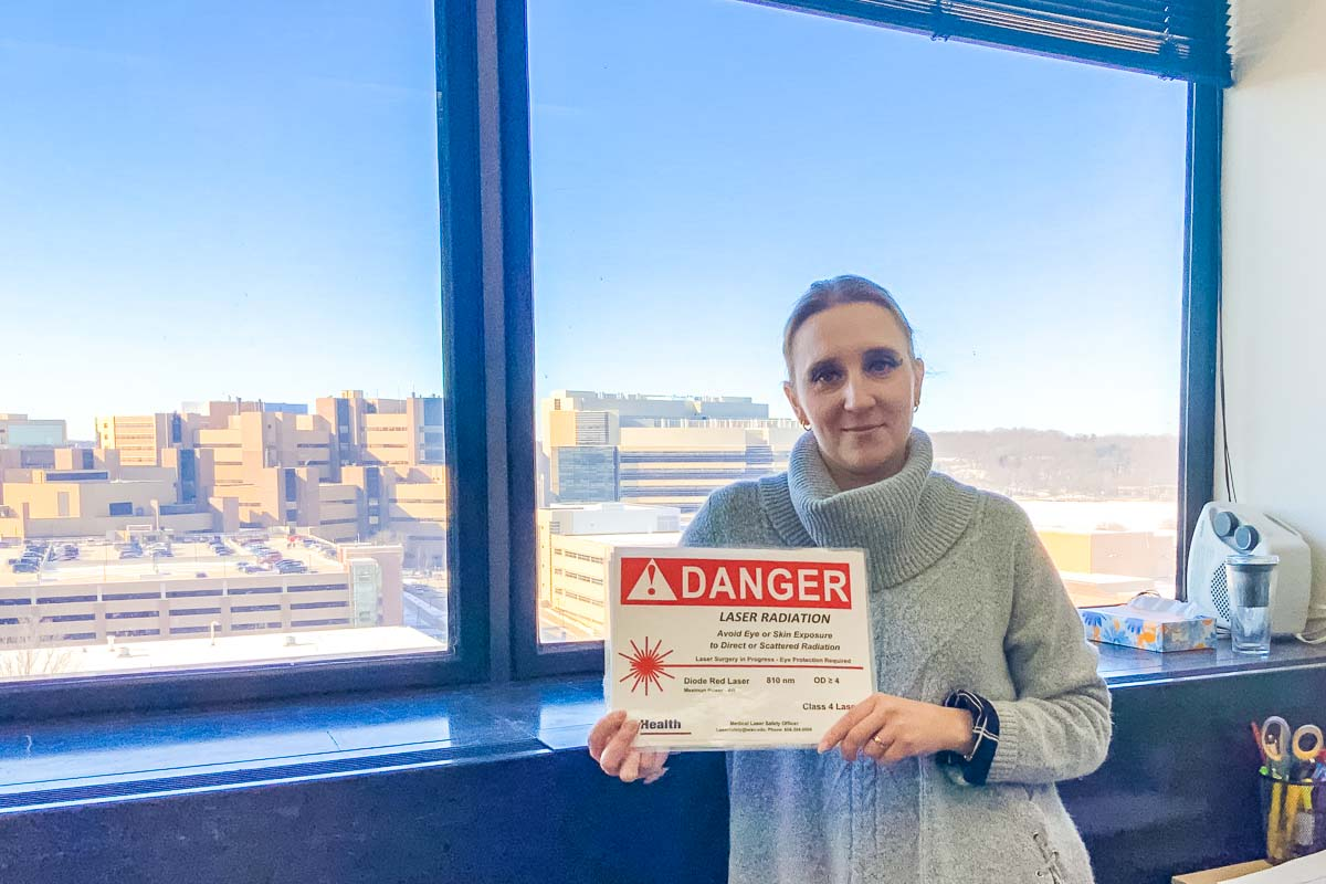 "Woman holds ""DANGER"" sign regarding laser safety while standing in front of a window view of campus"