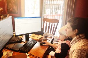 Human resources employee and daughter sitting by computer monitors as she works from home