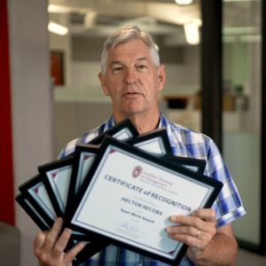 Alan holding up five award certificate plaques