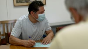 Photo: Benito sits at conference room table holding paper and a pen, talking and smiling while wearing a face covering