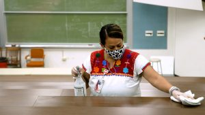 Juana cleans a lecture hall table with a rag and spray bottle. She is standing in front of a large chalkboard and wearing a face covering
