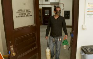 Photo: Mingur is walking into a classroom doorway while holding cleaning tools and wearing a face covering