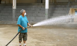 Todd using a large hose to spray the stock pavilion floor while wearing a face covering