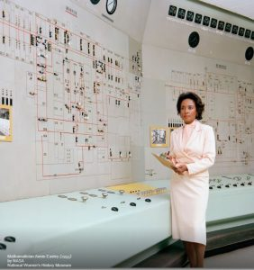 woman in NASA room with equipment and calculations
