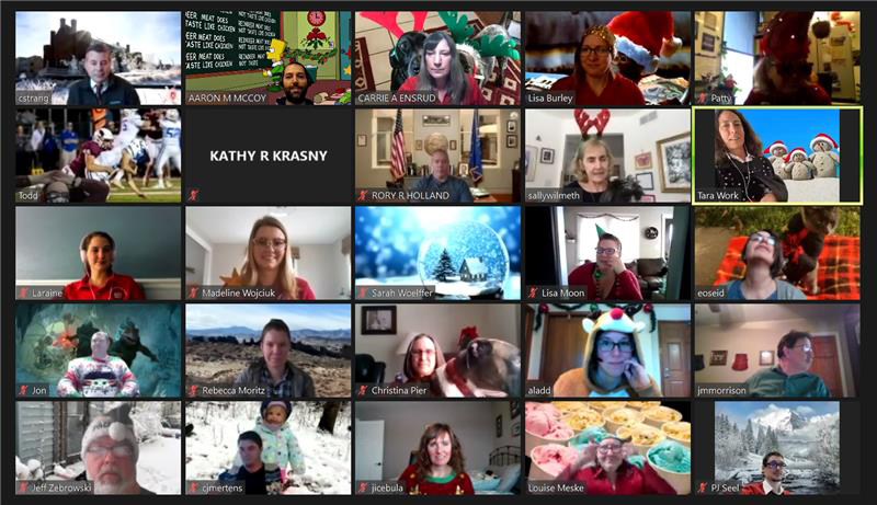 Screenshot of video conference call with many people's faces. Dressed in holiday outfits