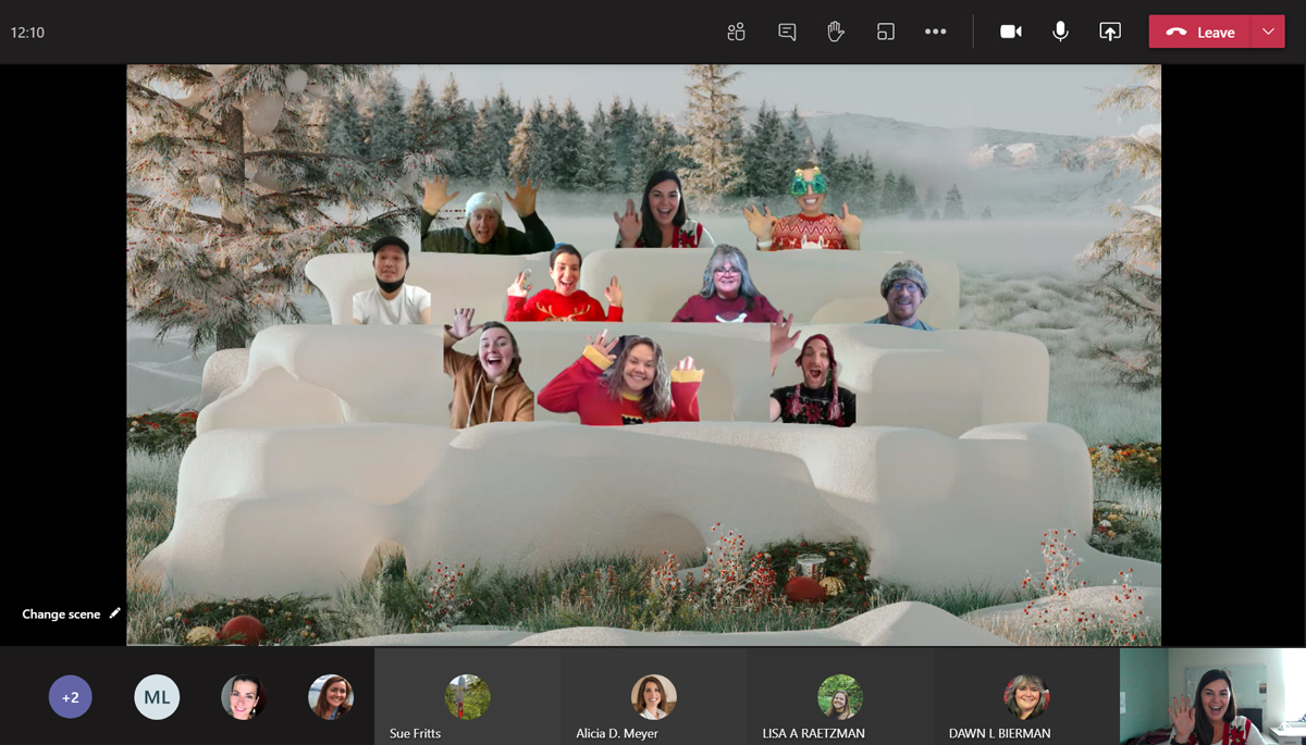 Screen shot of video conference call with 10 people smiling and posting while dressed in winter holiday outfits with an outdoor background