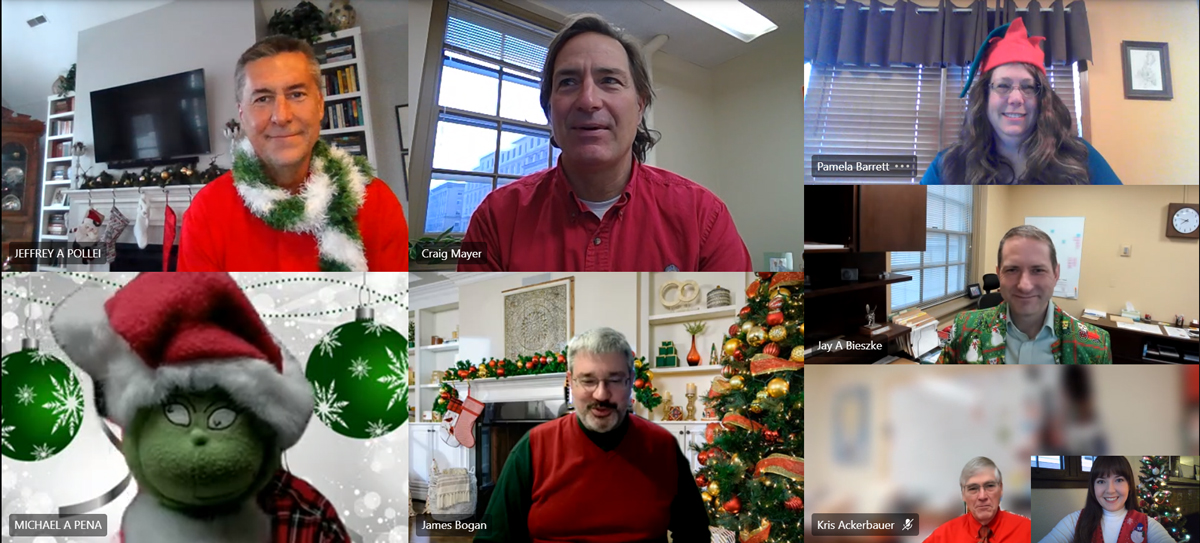 Screenshot: seven people from FP&M Physical plant seated and dressed in holiday outfits on a video conference call