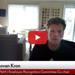 """video player: Donovan Kron is seated at home office speaking. Video play button. """"Donovan Kron, FP&M Employee Recognition Committee"""""""