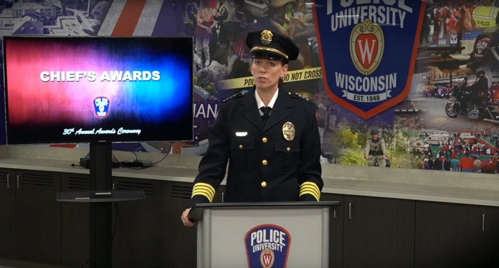 """Photo: A formally uniformed UW Police Officer stands in front of a podium beside a screen that reads """"Chief's Award"""""""
