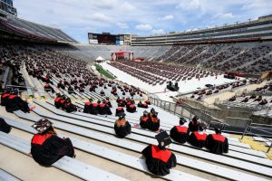photo: students wearing graduation caps sit far apart in Camp Randall Stadium for 2021 Commencement